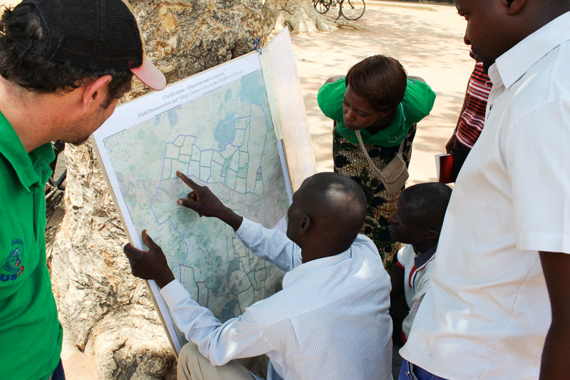 Precious Zulu (Chipata District Land Alliance) and Matt Sommerville (USAID) explore a map of land ownership in Kalichero, Zambia with local stakeholders.